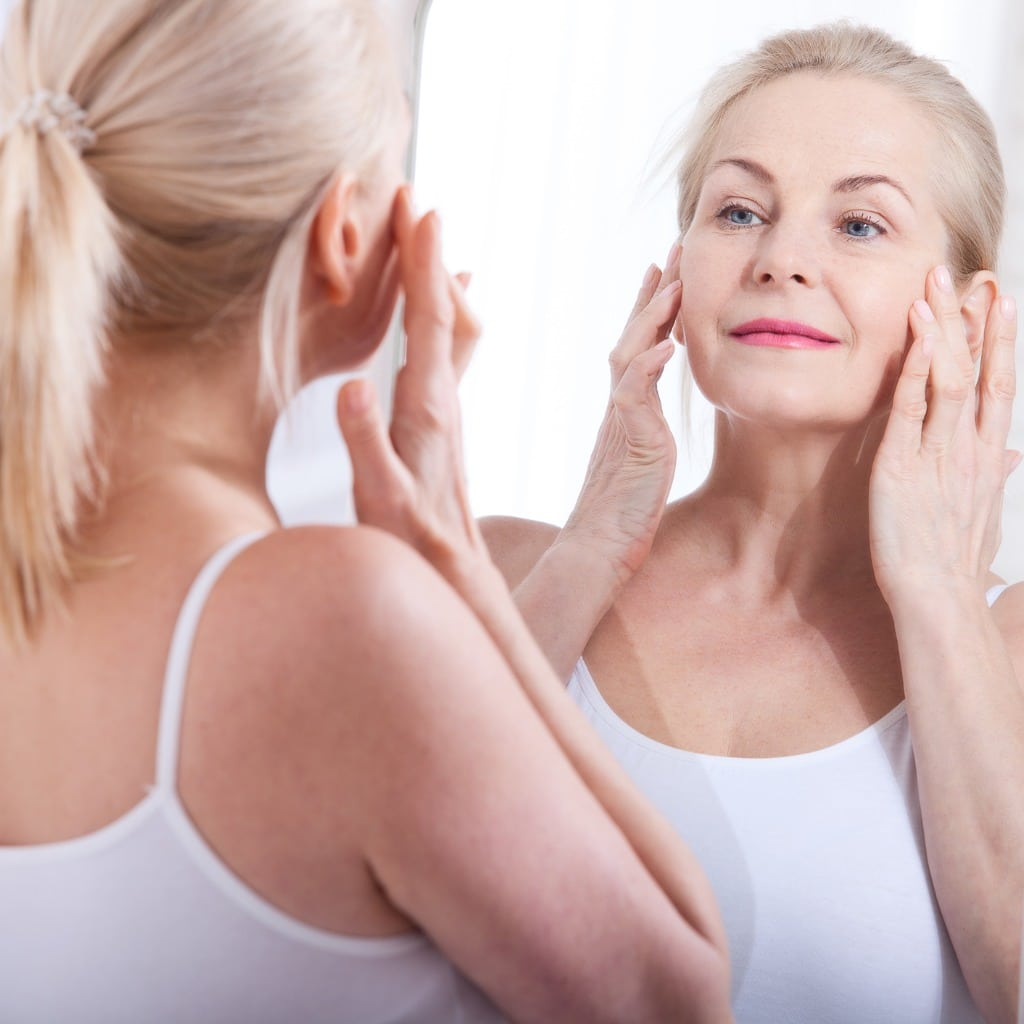 Middle Aged Woman Staring at Smooth Skin in Mirror